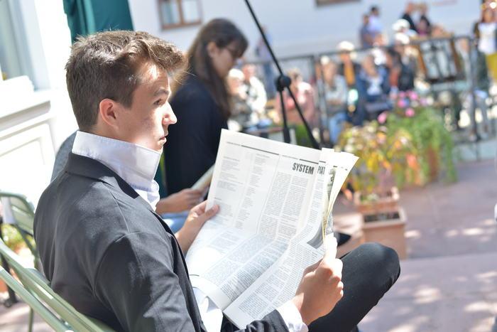 Bohater dramatu - Zbyszko Dulski, siedząc na ławce czyta gazetę.