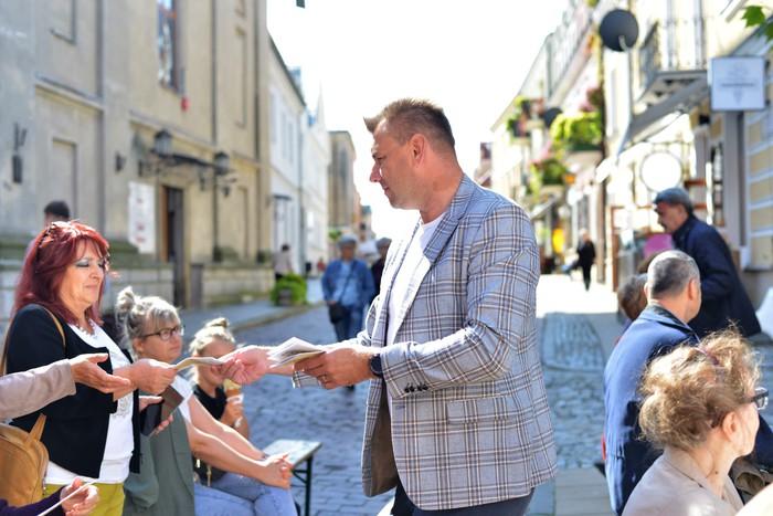 Marcin Marzec Burmistrz Sandomierza rozdaje widowni informatory o wydarzeniu.