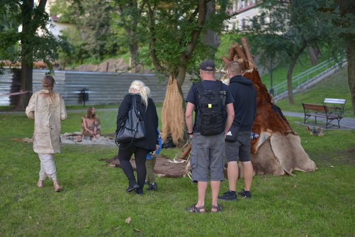 Turyści zwiedzają wioskę neolityczną.