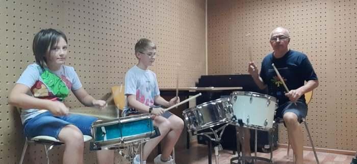 Uczestnicy warsztatów muzycznych ćwiczą grę na perkusji wraz z instruktorem.