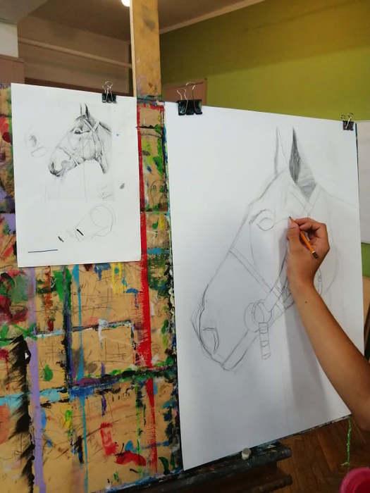 Uczestnicy warsztatów rysują podczas zajęć.