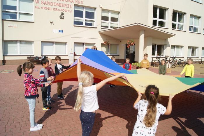 Dzieci bawią się kolorową chustą.
