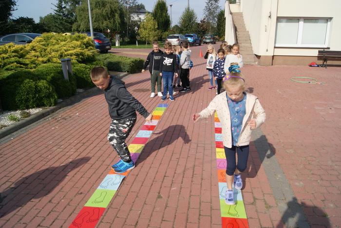 Dzieci skaczą po kolorowych ścieżkach podczas zajęć integrujących.