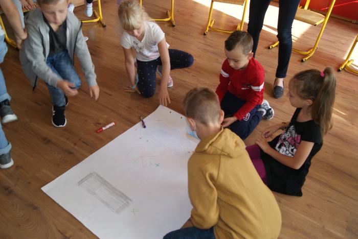 Dzieci tworzą plakat podczas zajęć integrujących.