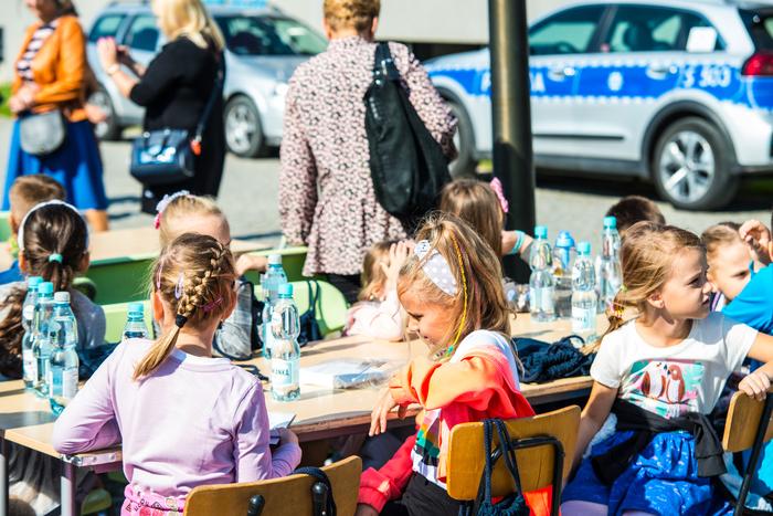 02. Siedzące przy stole dzieci rozmawiają ze sobą
