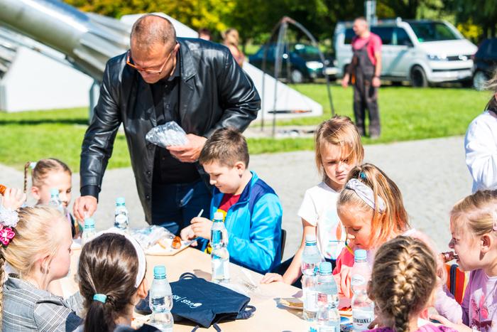 20. Dzieci jedzą przy stole kiełbaski