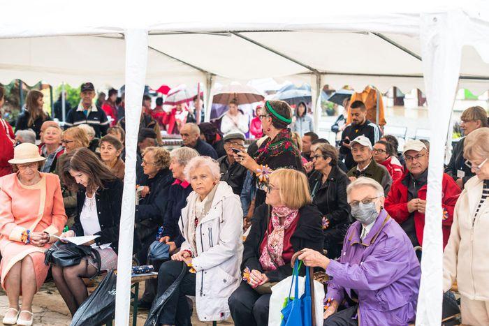 10. Seniorzy siedzący pod namiotem słuchają wystąpienia burmistrza