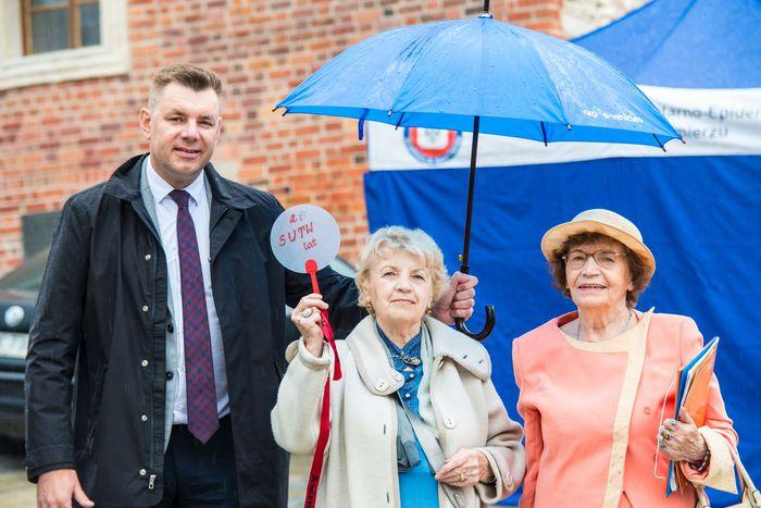 20. Burmistrz pozuje do zdjęcia z seniorkami, trzymając nad nimi parasol podczas deszczu
