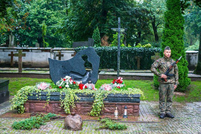 18. Mogiła w asyście żołnierza ze złożonymi wiązankami kwiatów