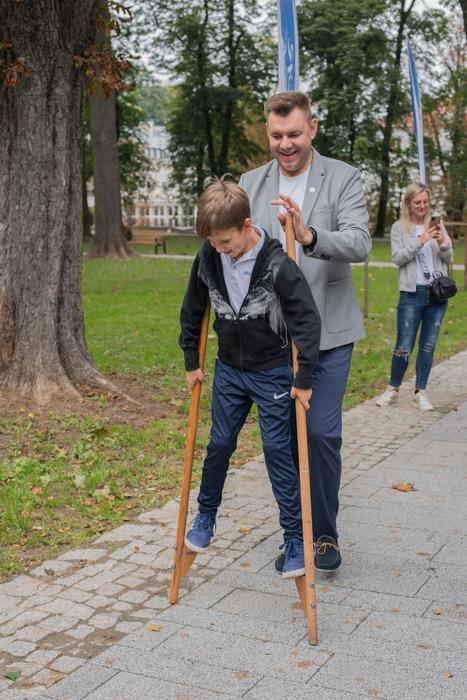 Burmistrz Sandomierza prowadzi syna na szczudłach