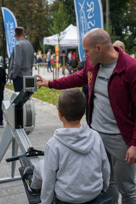 pracownik MOSiRu ustawia sprzęt sportowy chłopcu