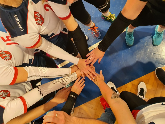 Zdjęcie przedstawia połączone ręce sandomierskiej drużyny siatkarek.