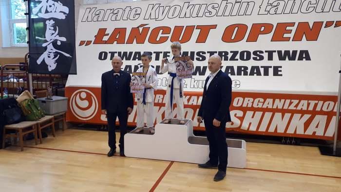 Nagrodzeni uczestnicy mistrzostw stoją na podium.
