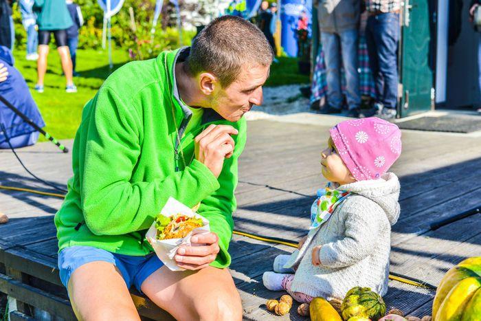 16. Na zdjęciu mężczyzna jedzący posiłek, obok niego siedzi małe dziecko